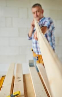 Starszy stolarz trzyma drewnianą deskę
