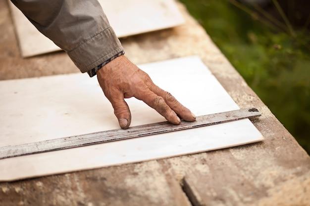 Starszy stolarz w podeszłym wieku, używając linii prostej do rysowania linii na desce.