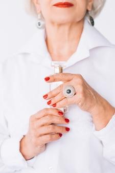 Starszy styl moda kobieta. trendy w perfumach. butelka drogiego zapachu w kobiecych rękach.
