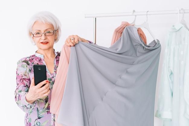 Starszy stylista mody. udany biznes butikowy. starsza pani udzielająca porad dotyczących dopasowywania kolorów