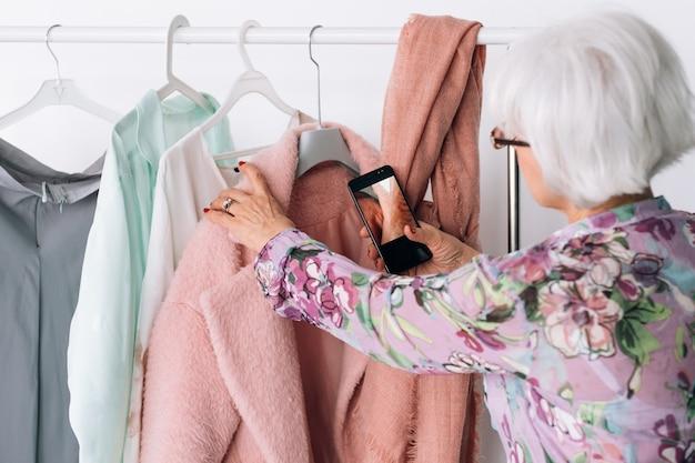 Starszy stylista mody w pracy. pani udanego biznesu. starsza kobieta biorąc zdjęcie mobilne. spersonalizowana usługa zakupów.