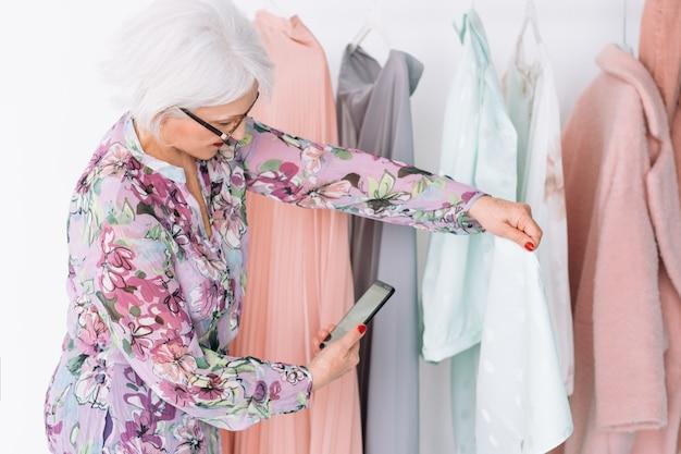 Starszy stylista mody w pracy. udana starsza dama biznesu kręcenie vloga. spersonalizowana usługa zakupów.