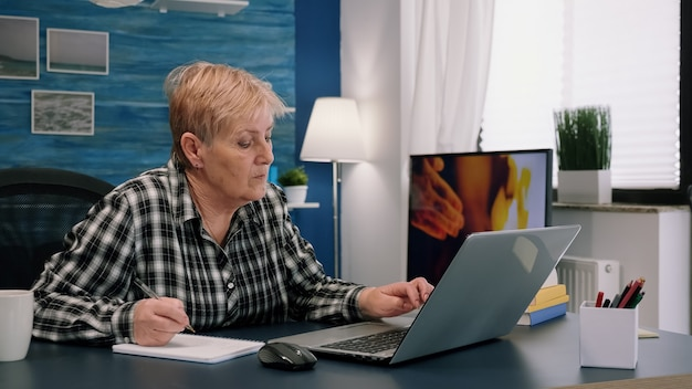 Starszy stylowa kobieta robienia notatek w notebooku podczas korzystania z laptopa w domu. stary freelancer piszący szczegóły na książce podczas pracy z obszaru roboczego w salonie, sprawdzający projekt finansowy firmy
