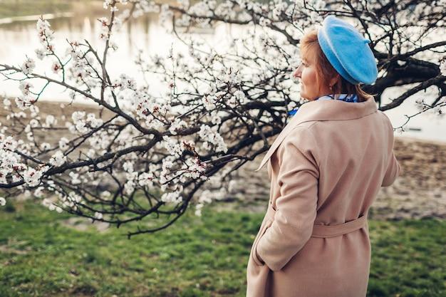 Starszy stylowy kobiety odprowadzenie w wiosny kwitnienia ogródzie rzeką podziwia natura krajobraz. dzień matki