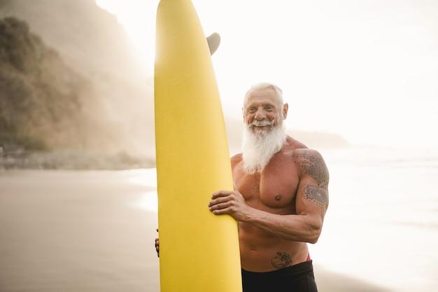 Starszy surfer trzymający deskę surfingową na plaży o zachodzie słońca - skup się na twarzy