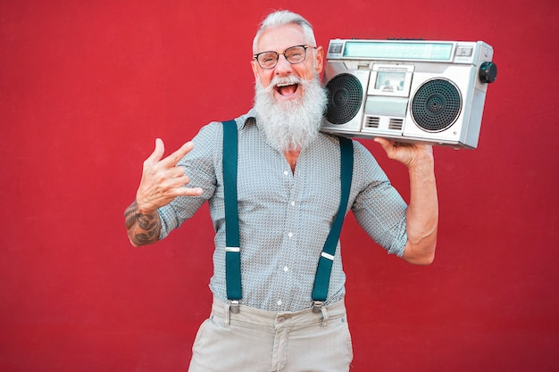 Starszy szalony człowiek z boomboxem z lat 80. odtwarzający muzykę rockową na czerwonym tle - modny dojrzały facet świetnie się bawi tańczący z radiem w stylu vintage - radosny styl życia w podeszłym wieku - skup się na twarzy