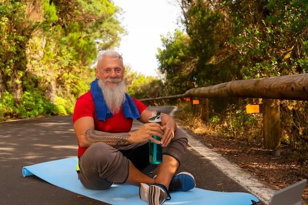 Starszy szczęśliwy uśmiechnięty mężczyzna z białą brodą odpoczywa podczas wykonywania ćwiczeń na świeżym powietrzu na przyrodę