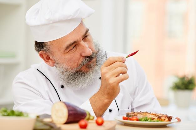 Starszy szef kuchni trzyma papryczki chili