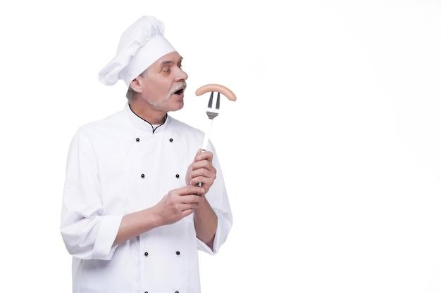 Starszy szef rzeźnika w mundurze kucharza uśmiechający się, trzymając kiełbasę na widelcu, odizolowany na białej ścianie