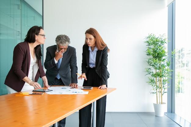 Starszy szef w okularach ogląda statystyki i omawia projekt z partnerami. zadowoleni odnoszący sukcesy biznesmeni stojący w pobliżu stołu z tabletami i papierami i rozmawiający. biznes i współpraca con