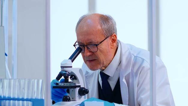 Starszy technik laboratoryjny badający próbki i ciecz za pomocą mikroskopu w wyposażonym laboratorium. naukowiec pracujący z różnymi bakteriami, próbkami tkanek i krwi, badania farmaceutyczne nad antybiotykami