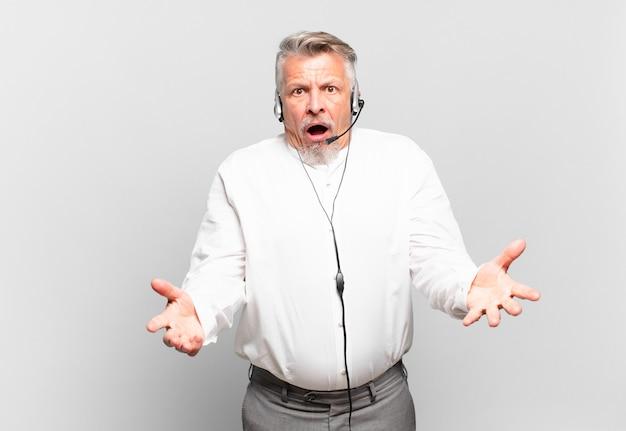 Starszy telemarketer czujący się niezwykle zszokowany i zaskoczony, niespokojny i spanikowany, o zestresowanym i przerażonym spojrzeniu