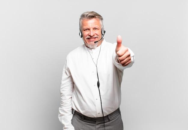 Starszy telemarketer czuje się dumny, beztroski, pewny siebie i szczęśliwy, uśmiecha się pozytywnie z kciukami w górę