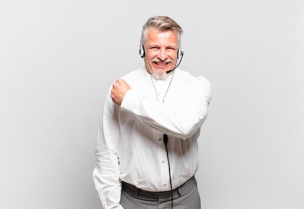 Starszy telemarketer czuje się szczęśliwy, pozytywnie nastawiony i odnosi sukcesy, jest zmotywowany, gdy staje przed wyzwaniem lub świętuje dobre wyniki