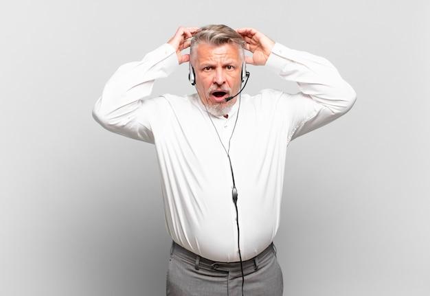 Starszy telemarketer czuje się zestresowany, zmartwiony, niespokojny lub przestraszony, z rękami na głowie, panikujący z powodu błędu