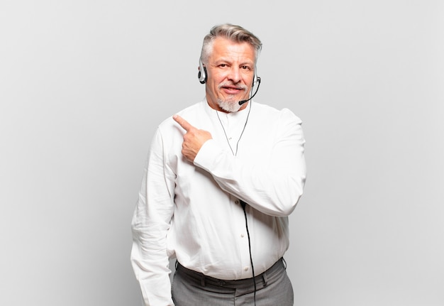 Starszy telemarketer uśmiecha się radośnie, czuje się szczęśliwy i wskazuje na bok i do góry, pokazując obiekt w przestrzeni kopii