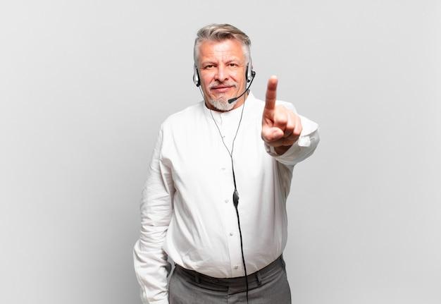 Starszy telemarketer uśmiechający się dumnie i pewnie wykonując triumfalną pozę numer jeden, czując się jak lider