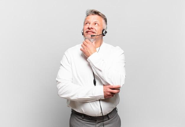 Starszy telemarketer uśmiechnięty radośnie i marzący lub wątpiący, patrzący w bok