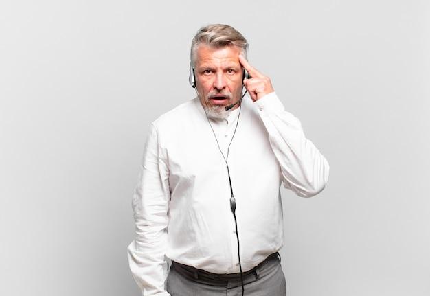 Starszy telemarketer wygląda na zaskoczonego, z otwartymi ustami, zszokowanego, realizującego nową myśl, pomysł lub koncepcję