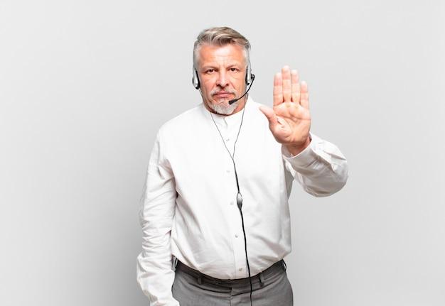 Starszy telemarketer wygląda poważnie, surowo, niezadowolony i zły pokazując otwartą dłoń, wykonując gest zatrzymania