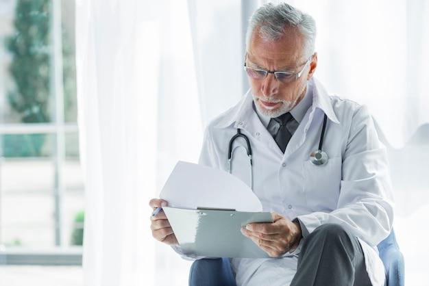 Starszy terapeuta czytając zapisy