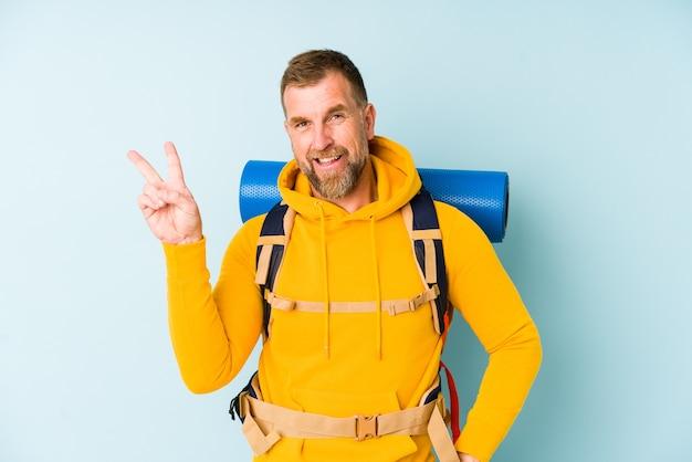 Starszy turysta mężczyzna na białym tle na niebieskiej ścianie radosny i beztroski pokazujący palcami symbol pokoju.
