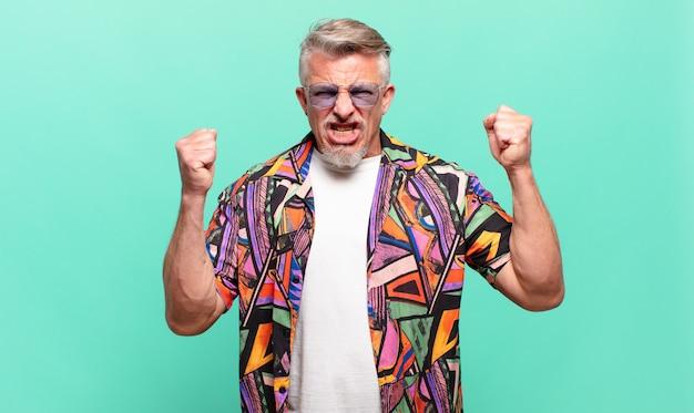 Starszy turysta podróżujący agresywnie krzyczący z gniewnym wyrazem twarzy lub z zaciśniętymi pięściami świętujący sukces