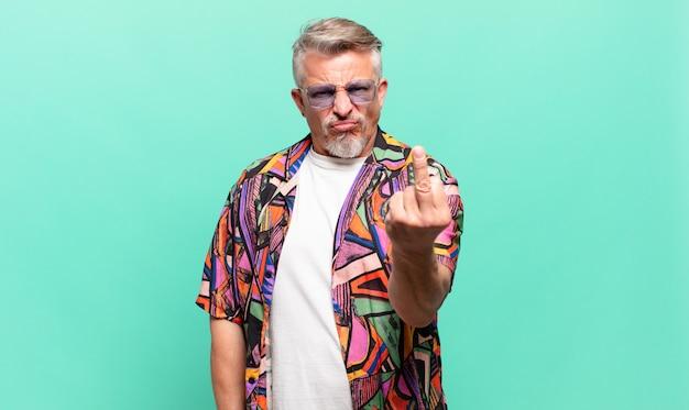 Starszy turysta podróżujący czuje się zły, zirytowany, zbuntowany i agresywny, macha środkowym palcem, walczy