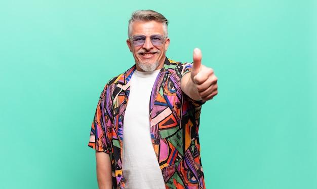 Starszy turysta podróżujący dumny, beztroski, pewny siebie i szczęśliwy, uśmiechnięty pozytywnie z uniesionymi kciukami