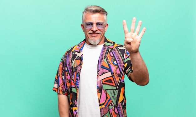 Starszy turysta podróżujący uśmiechnięty i przyjazny, pokazujący numer cztery lub czwarty z ręką do przodu, odliczający w dół