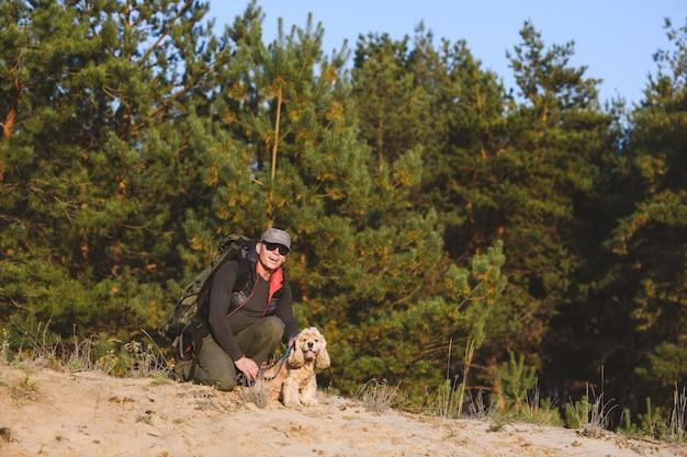 Starszy turysta z plecakiem klęczy w lesie z psem