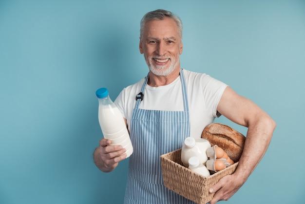 Starszy, uroczy mężczyzna trzyma koszyk artykułów spożywczych w drugiej ręce butelkę mleka
