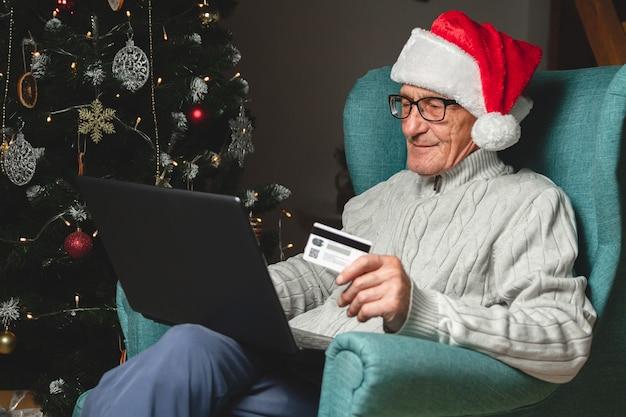 Starszy w kapeluszu świętego mikołaja siedzi w fotelu za pomocą laptopa hoding karty kredytowej