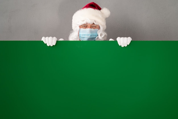 Starszy w stroju świętego mikołaja i masce ochronnej. człowiek posiadający zielony pusty deska. święta bożego narodzenia podczas pandemii koronawirusa covid 19