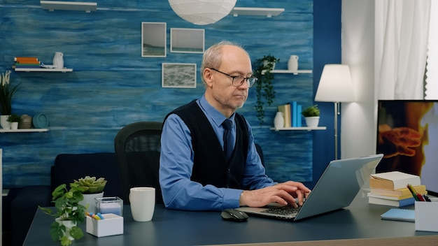 Starszy zdalny biznesmen otwierający laptopa i czytający raporty, pracujący w domu, pijący kawę