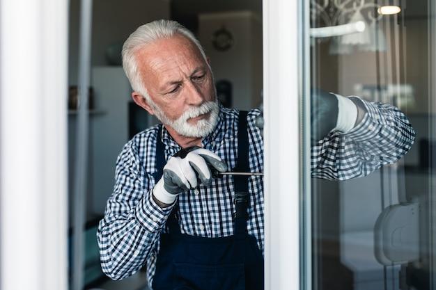 Starszy złota rączka naprawianie okna. renowacja.