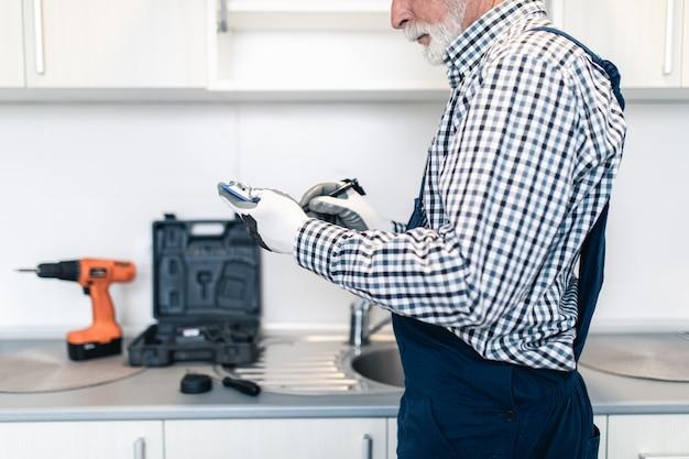 Starszy złota rączka pisania rachunku za usługi remontu kuchni.