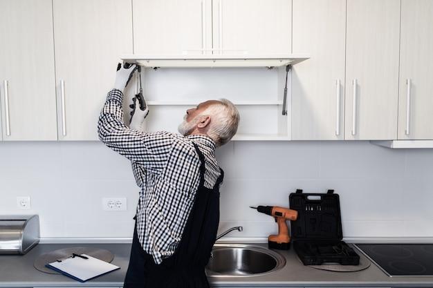 Starszy złota rączka pracuje w kuchni. renowacja.