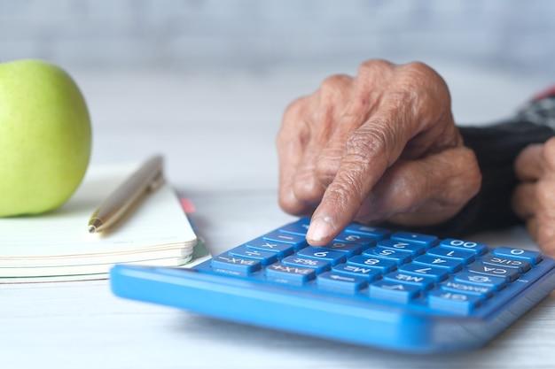 Starszych kobiet ręcznie za pomocą kalkulatora na biurku