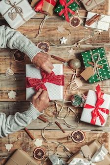 Starszych rąk starszego mężczyzny pakowania prezentów świątecznych na stole z dekoracjami świątecznymi