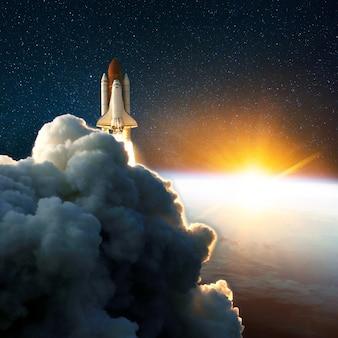 Start rakiety, start o niesamowitym zachodzie słońca. prom kosmiczny w przestrzeni w pobliżu ziemi z żółtym wschodem słońca. chmury i niebo na tle. sukces rozpocznij misję kosmosu
