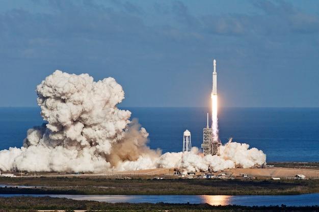 Start rakiety z księżycem w tle. elementy tego zdjęcia dostarczone przez nasa