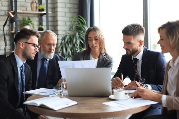 Startowy zespół biznesowy na spotkanie w nowoczesnym, jasnym wnętrzu biurowym i pracy na laptopie.
