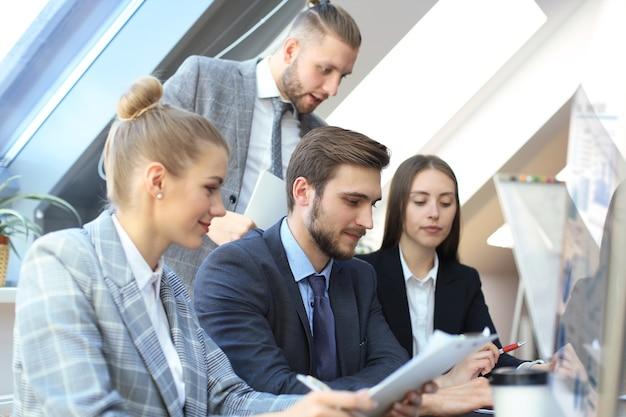 Startowy zespół biznesowy na spotkaniu w burzy mózgów w nowoczesnym, jasnym wnętrzu biurowym, pracujący na komputerach typu tablet i pc.