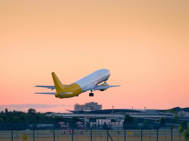 Startujący samolot z pasa startowego o zachodzie słońca