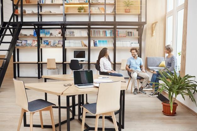 Startup, biznes, koncepcja pracy zespołowej. grupa perspektywicznych młodych ludzi spotykających się w dużej nowoczesnej bibliotece, rozmawiających o zyskach z ostatniego projektu, przeglądających papiery, uśmiechających się i produkujących czas