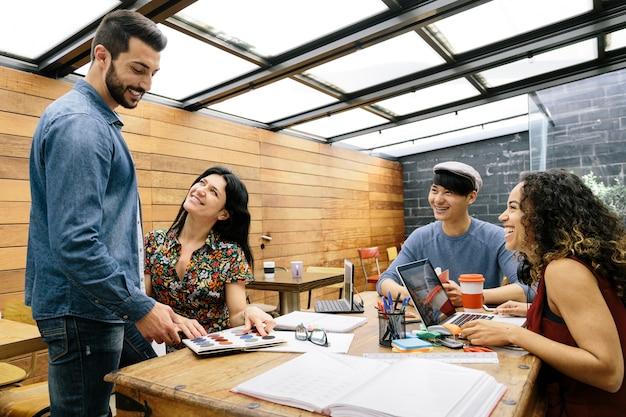 Startup czterech wieloetnicznych osób radośnie dyskutujących o pomysłach w nowoczesnej przestrzeni coworkingowej