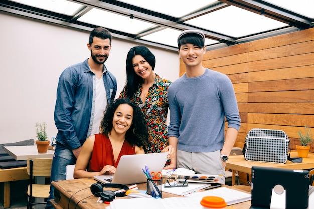 Startup czterech wieloetnicznych szczęśliwych ludzi w nowoczesnej przestrzeni coworkingowej