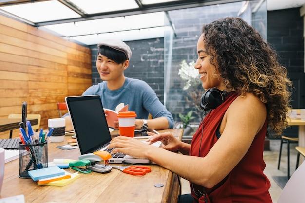 Startup dwóch wieloetnicznych osób radośnie dyskutujących o pomysłach w nowoczesnej przestrzeni coworkingowej