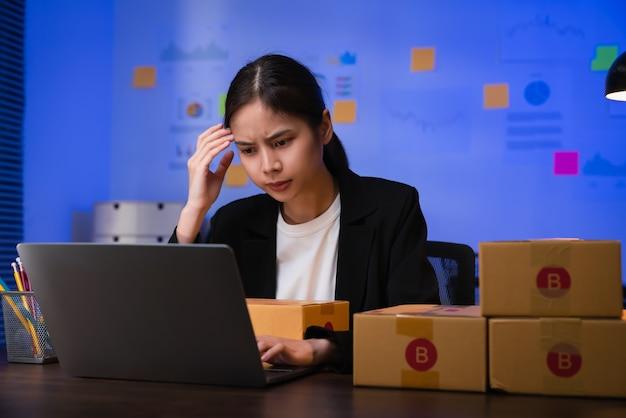 Startup koncepcja małego biznesu, młoda kobieta właścicielka rąk dotyka czoła ma ból głowy z powodu stresu i sprawdza zamówienie online na laptopie cyfrowym z pakowaniem na pudełku w biurze domowym.